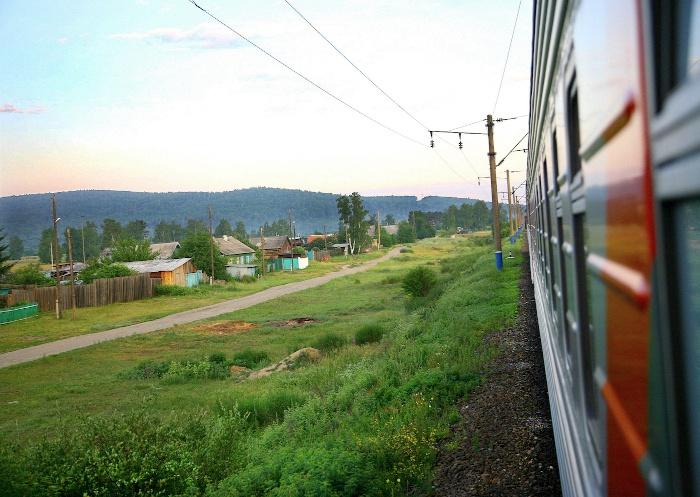 Die Transsibirische Eisenbahn während sie an einem Dorf vorbei fährt
