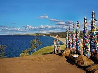 Holzpfeiler mit Gebetsfahnen am Ufer des Baikalsees