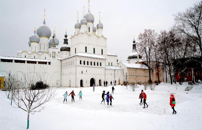 Kinder laufen Schlittschuh auf einem zugefrorenen Teich inmitten eines beschneiten Klosters in Russland