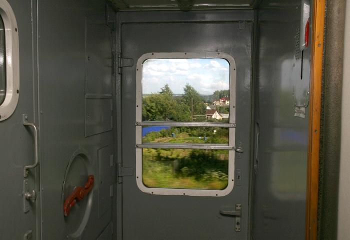 Zugfenster in der Transsibirischen Eisenbahn an dem ein kleines Dorf vorbeizieht