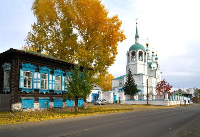 Ein verziertes Holzhaus neben einer kleinen Kirche in Jenisejsk