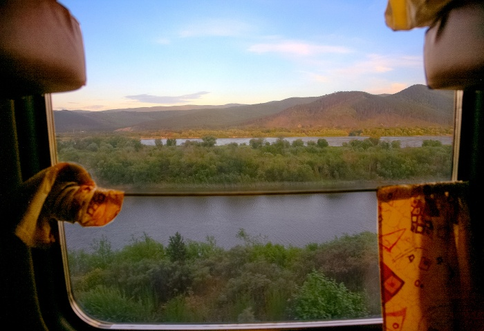 Abteilfenster der Transmongolischen Eisenbahn mit Ausblick auf einen Fluß