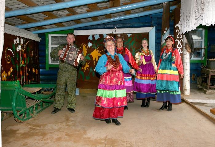 Altgläubige Frauen tanzen in traditioneller Kleidung zu einem Akkordion