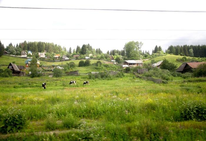 Ein Holzdorf auf Hügeln die an der Transsib liegen