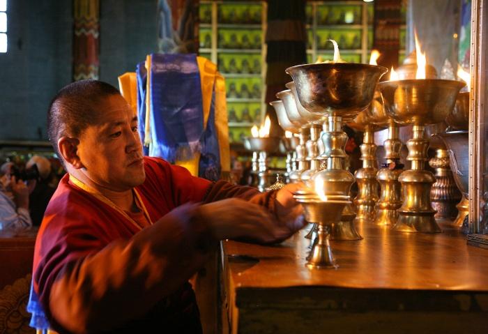 Buddhistischer Mönch stellt Kerzen auf in einem Tempel in Ulan-Bator