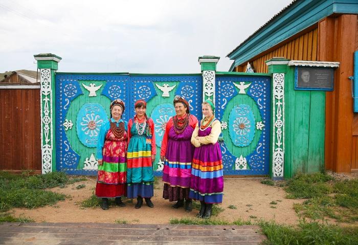 Altgläubige Frauen in traditionellen Kleidern vor einem verzierten Holzhaus