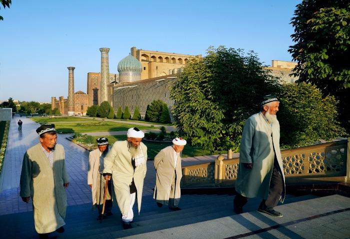 Traditionell gekleidete Usbeken vor dem Registan in Samarkand