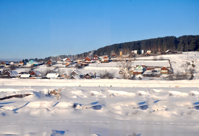 Sibirisches Dorf im Tiefschnee an der Transsibirischen Eisenbahn